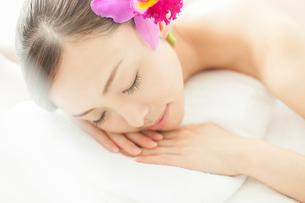 耳元に花を挿し枕にうつ伏せになり目を閉じる女性の写真素材 [FYI01418222]