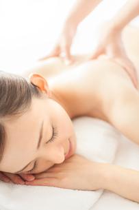 ベッドにうつ伏せで背中にマッサージを受ける女性の写真素材 [FYI01418298]