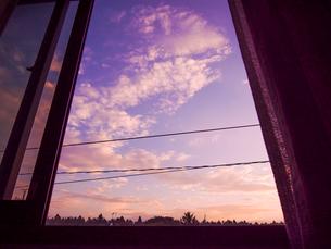 窓を開け放ち朝焼けの空を眺めるの写真素材 [FYI01418416]