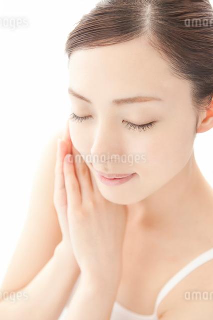頬に手を重ね目を閉じ微笑む女性の写真素材 [FYI01418431]
