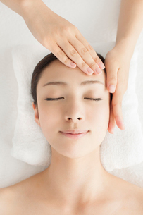 ベッドに仰向けで顔にマッサージを受ける女性の写真素材 [FYI01418452]