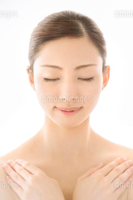 胸元に手を組んで目を閉じる女性の写真素材 [FYI01418455]