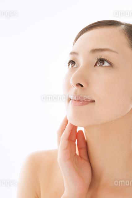 頬に手を寄せて上を見つめる女性の写真素材 [FYI01418507]