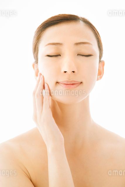 頬に手をあて目を閉じる女性の写真素材 [FYI01418512]