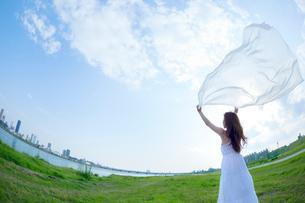 都会の青空の下で白い布を広げる女性の写真素材 [FYI01418518]
