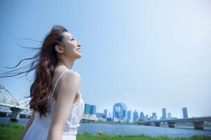 都会の青空の下で空を見上げる女性の写真素材 [FYI01418524]