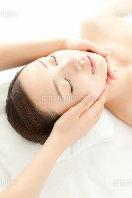 ベッドに仰向けで顔にマッサージを受ける女性の写真素材 [FYI01418650]