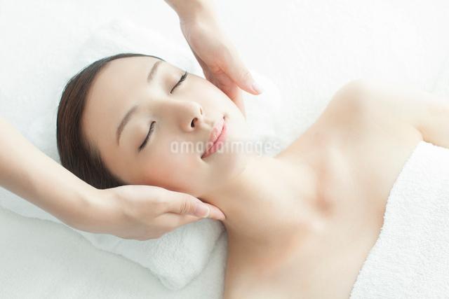 ベッドに仰向けで顔にマッサージを受ける女性の写真素材 [FYI01418672]