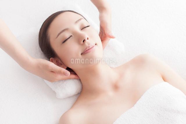 ベッドに仰向けで首にマッサージを受ける女性の写真素材 [FYI01418755]