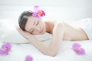 耳元に花を挿し枕にうつ伏せになり目を閉じる女性の写真素材 [FYI01418757]