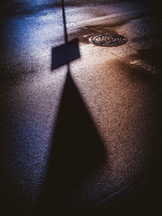 シルエットを映す雨上がりの路面反射の写真素材 [FYI01418784]