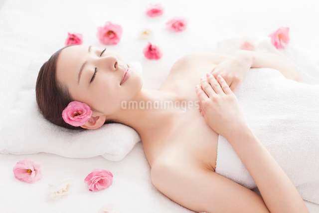 耳元に花を挿し胸前で手を組みベッドに仰向けになる女性の写真素材 [FYI01418793]