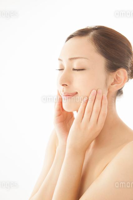 頬に両手をあてる女性の写真素材 [FYI01418797]