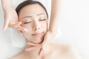 ベッドに仰向けで顔にマッサージを受ける女性の写真素材 [FYI01418823]