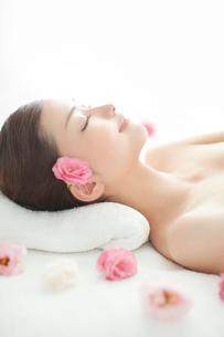 耳元に花を挿しベッドに仰向になり目を閉じる女性の写真素材 [FYI01418872]