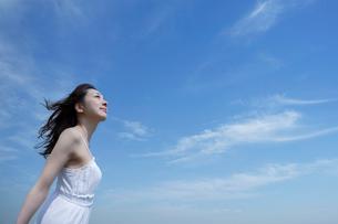 都会の青空の下で空を見上げる女性の写真素材 [FYI01418980]