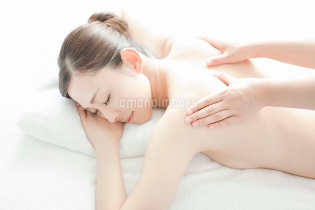 ベッドにうつ伏せで肩にマッサージを受ける女性の写真素材 [FYI01419048]