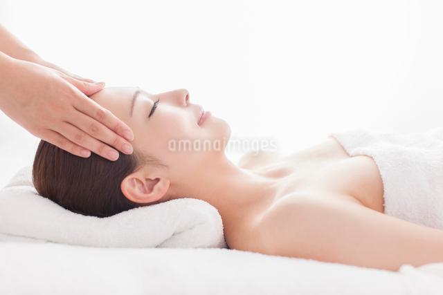 ベッドに仰向けで頭にマッサージを受ける女性の写真素材 [FYI01419098]