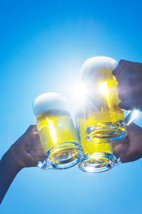 青空の中でジョッキビールで乾杯をする3人の写真素材 [FYI01419171]