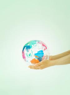 女性の手とクリスタルの地球儀の写真素材 [FYI01419360]