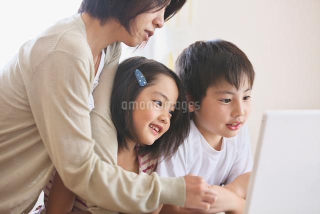 パソコンをする家族の写真素材 [FYI01419549]
