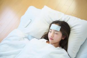 風邪で寝込んだ女の子の写真素材 [FYI01420472]