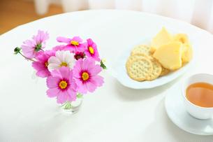 テーブルの上のコスモスとハーブティーとクッキーの写真素材 [FYI01420488]