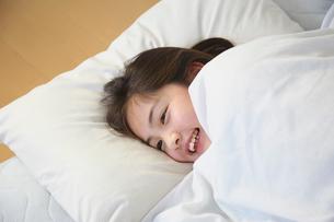 フトンに入って笑っている女の子の写真素材 [FYI01420640]