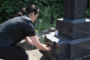 墓に線香をあげる女性の写真素材 [FYI01421016]