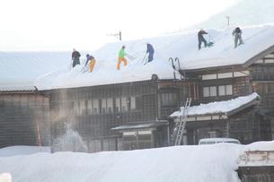 民家の雪下ろし風景の写真素材 [FYI01421528]