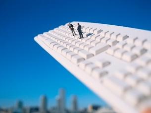 キーボードの上にいるビジネスマンの人形の写真素材 [FYI01422428]