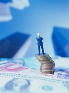紙幣とコインに乗る人形の写真素材 [FYI01422505]
