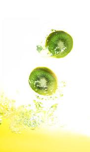 弾ける水しぶきと輪切りのキウイと果汁の写真素材 [FYI01422675]