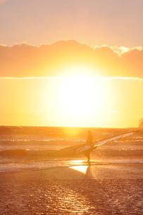 湘南海岸の夕景の中に立つサーファーの写真素材 [FYI01422677]
