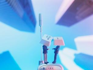 携帯電話の上のキーを被ったビジネスマンの人形の写真素材 [FYI01422815]