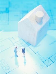 設計図の上の住宅模型と2体の人形の写真素材 [FYI01422960]