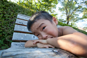 ベンチで泣く男の子の写真素材 [FYI01423469]