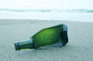 砂浜の光の当たった潰れた緑の瓶の写真素材 [FYI01423535]