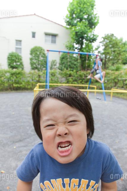 公園でおどけた表情をする男の子の写真素材 [FYI01423819]