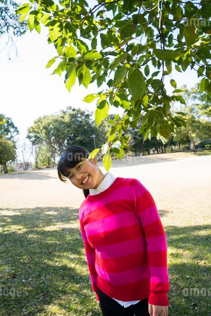 ピンク色のセーターを着て新緑の下微笑む女性の写真素材 [FYI01424230]