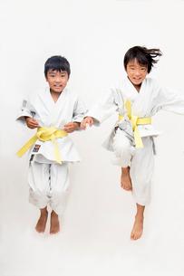 空手着姿で飛び上がる二人の子供の写真素材 [FYI01424243]