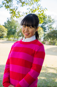 ピンク色のセーターを着て微笑む女性の写真素材 [FYI01424326]