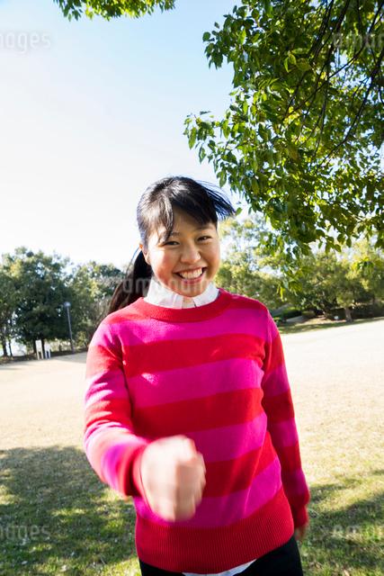 ピンク色のセーターを着て元気に手を振る女性の写真素材 [FYI01424559]