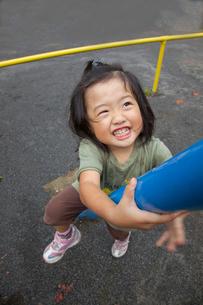 鉄棒に登って遊ぶ少女の写真素材 [FYI01425611]
