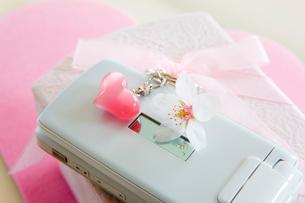 携帯電話と桜の花とハートのストラップの写真素材 [FYI01426051]