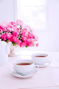 花瓶のピンクのバラと紅茶の写真素材 [FYI01426965]