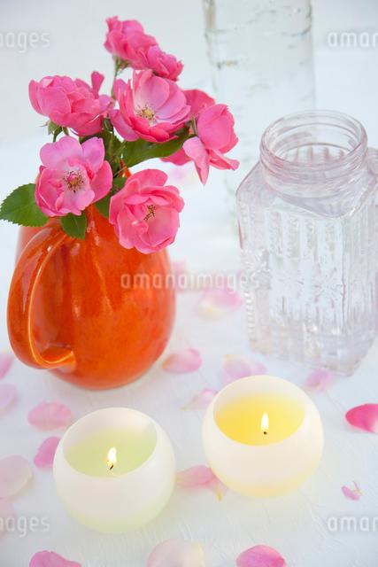 オレンジ色の水差しに入ったバラの花とキャンドルの写真素材 [FYI01427166]
