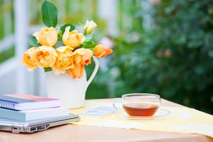 庭のテーブルの紅茶とパソコンとノートと黄色いのバラの花の写真素材 [FYI01427517]