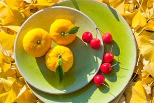 グリーンの皿の上のユズと姫リンゴとイチョウの落葉の写真素材 [FYI01427803]