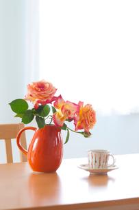 赤い水差しのバラの花とコーヒーカップの写真素材 [FYI01428147]
